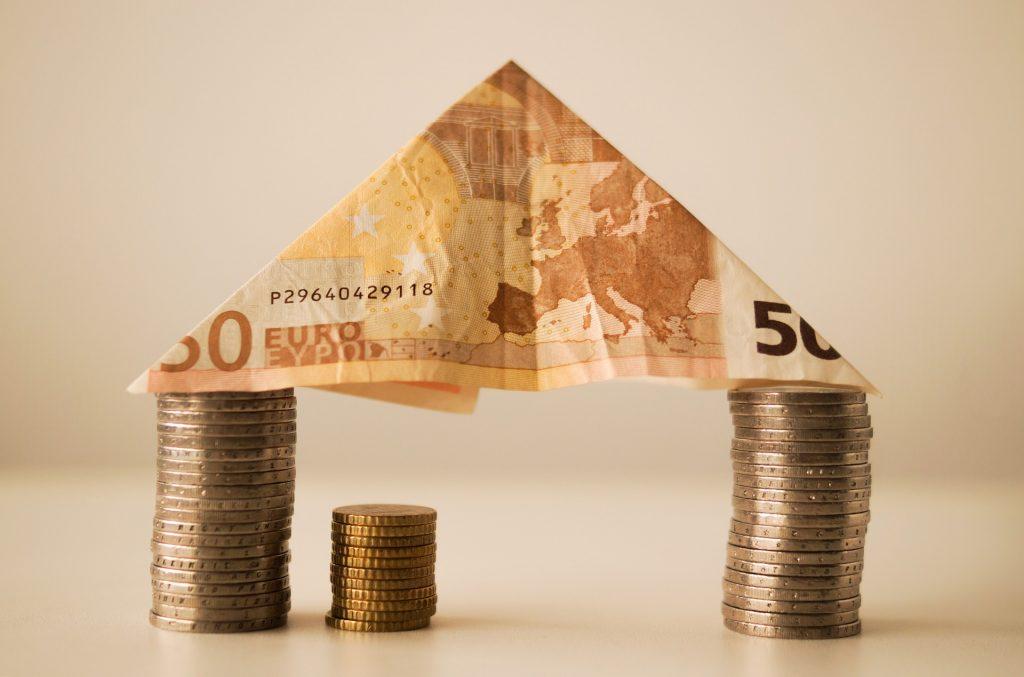 gestalpelte Euromünzen mit Geldschein als Dach
